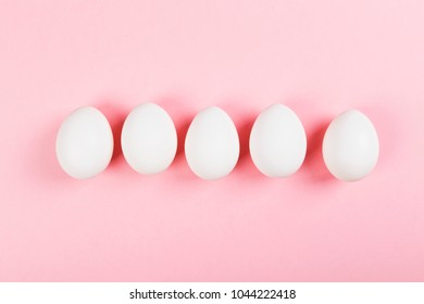 White egg on pink background. Top view