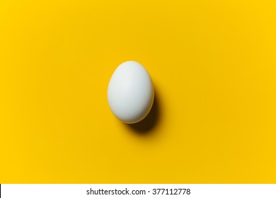 White egg on the yellow background in center. Design, visual art, minimalism
