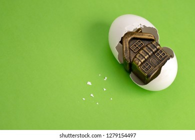 White egg shell with a golden toy building inside. Souvenir house in a broken egg. Green background. Copy space. The concept of the birth of a mortgage or loan for housing.