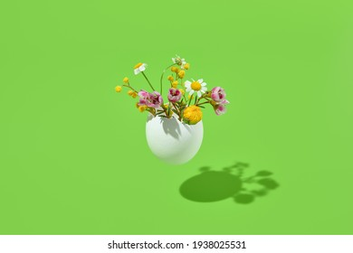 White egg and spring flowers bouquet. Easter minimal gift on green background. Happy easter, spring or summer, food conceptual layout
