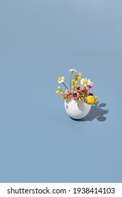 White egg and spring flowers. Easter egg minimal on pastel blue background. Happy easter, spring or summer, food concept