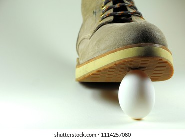 White egg under the sole of a boot. Concept of risky situation.