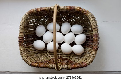 white egg in wicker basket on white background, top view
