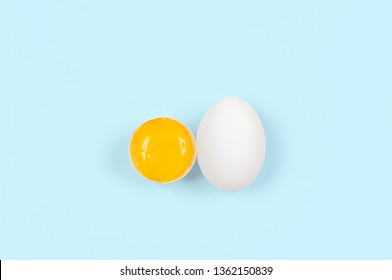 White egg and yolk.. Raw eggs on pastel blue background. Concept happy easter.