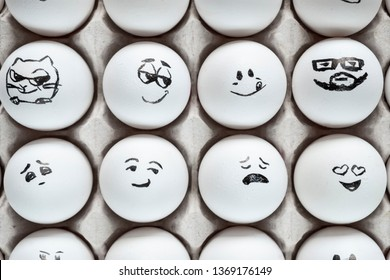 White eggs in cardboard box with different faces painted on them. Eggs with emotions.