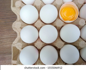 White eggs carton & cracked egg half with yolk top view on wooden background. Broken and whole eggs in carton box. Poultry eggs in carton paper tray package - healthy food breakfast cooking concept