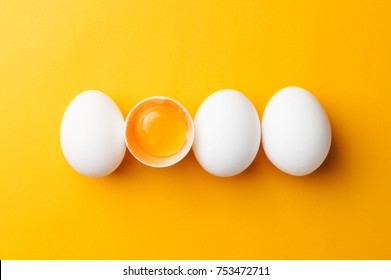 White eggs and egg yolk on the yellow background.