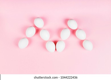 """White eggs in form of letter """"m"""" on pink background. Concept gender stereotypes, role of man and woman in society"""