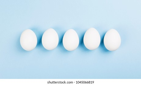 White eggs on blue background. Top view