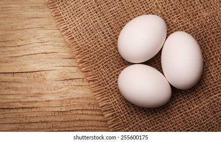 White eggs on burlap over wooden background