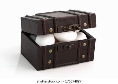 White eggs in a slightly open old fashion suit case