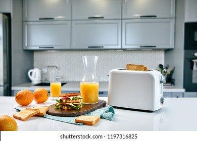 White electric bread toaster with orange juice with sandwich on kitchen table. Breakfast in the cozy kitchen.