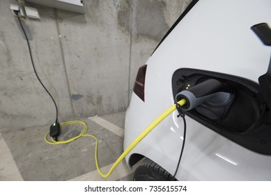 White Electric car charging in a house garage with power plug inserted