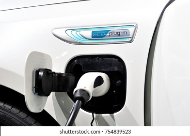 White electric car conected to charger.
