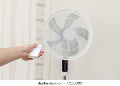 White electric fan turns on, turns off with the remote control.