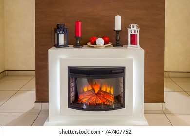 White electric fireplace with a fire, decorated with red and white candles, candlesticks, a plate with decorative balls