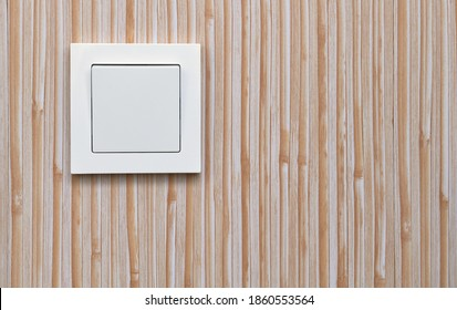 White electric light switch on the background of plastic wall panels. Home electricity.