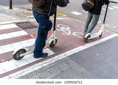 White electric scooters waiting in a bike lane.