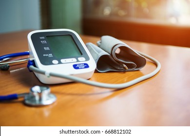 White electric tonometer on brown wooden table for measuring blood pressure with stethoscope Healthy concept