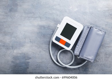 White electric tonometer on grey wooden table