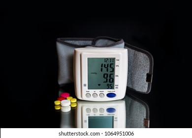 White electric wrist tonometer indicating blood pressure. Medicine, age, healthcare and people concept with tonometer and pills suggesting to take care of blood pressure.