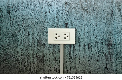 White electrical outlet on concrete wall background.