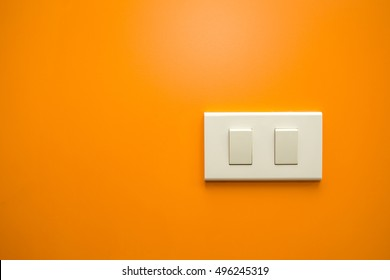 white electricity switch isolated on orange wall background with copy space