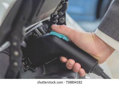 White electro car charging battery cells. Close up view of man hand charging electric vehicle.