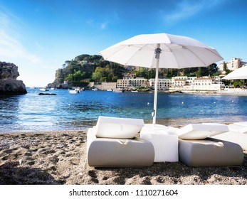 White elegant Sunbeds for romantic vacation at Mazzaro beach in Sicily Italy with hotels on the waterline and boats at the background