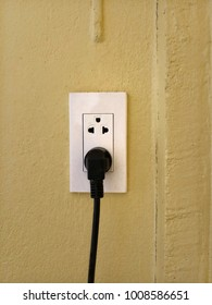white eletrical outlet socket and black cable pluged