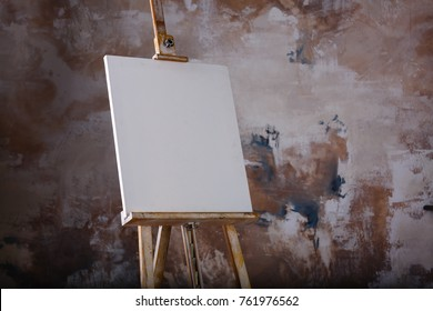 White empty artistic canvas on an easel for drawing images by an artist on a gray background