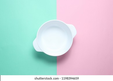 White empty bowl on pastel color background. Top view, minimalism