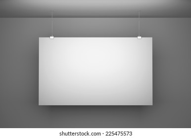 White empty canvas hanging by two chrome beams from a dark grey ceiling in front of a dark grey wall.