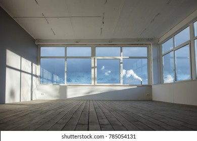 White empty loft interior with window shadow on the wall and wooden floors