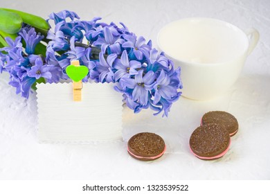 White empty mug on a background of spring flowers. Blue hyacinth lies in the background, a number of dishes and chocolate chip cookies, still life adorn cinnamon sticks. Nearby there is a paper card f
