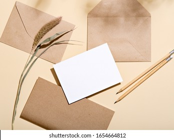 White empty paper card with stationery set of envelopes, notebook, pencil. Blank card styled mockup on beige background. To do list, greeting card or writing a letter concept. - Shutterstock ID 1654664812