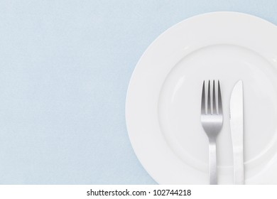 White empty plate with fork and knife on light blue tablecloth