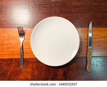 White empty plate, fork and knife on wooden texture background.