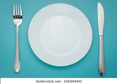 White empty plate with fork and knife on blue background. Turquoise backdrop. Laying, table appointments.