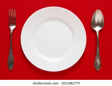 White empty plate with fork and spoon on a red tablecloth
