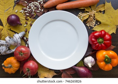 White empty plate with measuring tape and vegetables top view