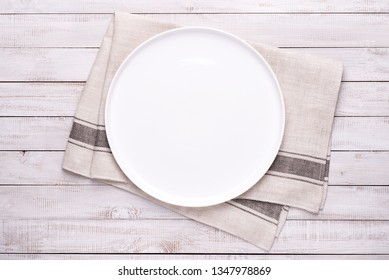 White empty plate on a kitchen towel on white wooden table, top view