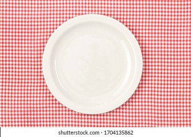 White empty plate on red checked tablecloth