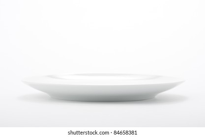 White empty plate on seamless white background.