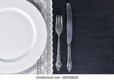 White empty plate on the tablecloth with lace, near knife and fork, top view