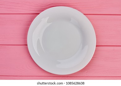 White empty plate on wooden background. Ceramic plate on pink wooden table, top view.