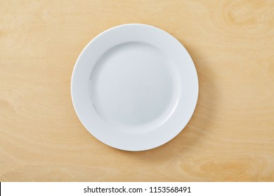 White empty plate on wooden table.