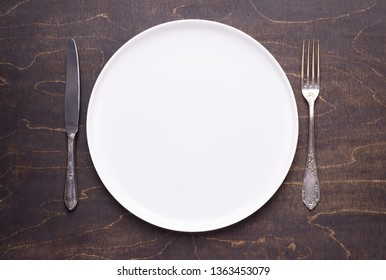 White empty plate on wooden table, top view