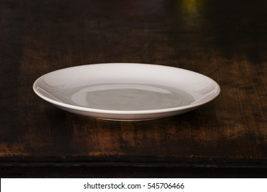 White Empty Plate on Wooden Brown Table.