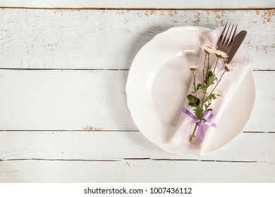 White empty plate, pink chrysanthemum flowers, napkin, fork and knife tied with a violet ribbon on light wooden background.
